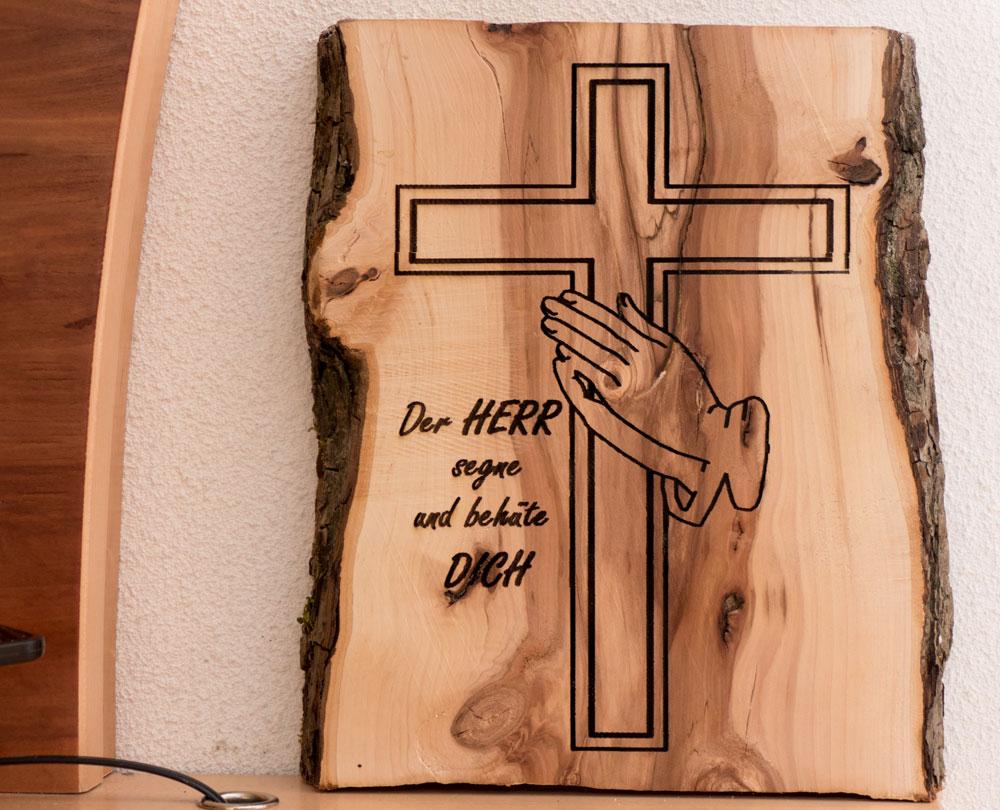Beschriftetes Kreuz auf einem Apfelbaumholz