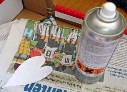 Mit einem Sprühkleber wird das Papierherz auf der Rückseite besprüht